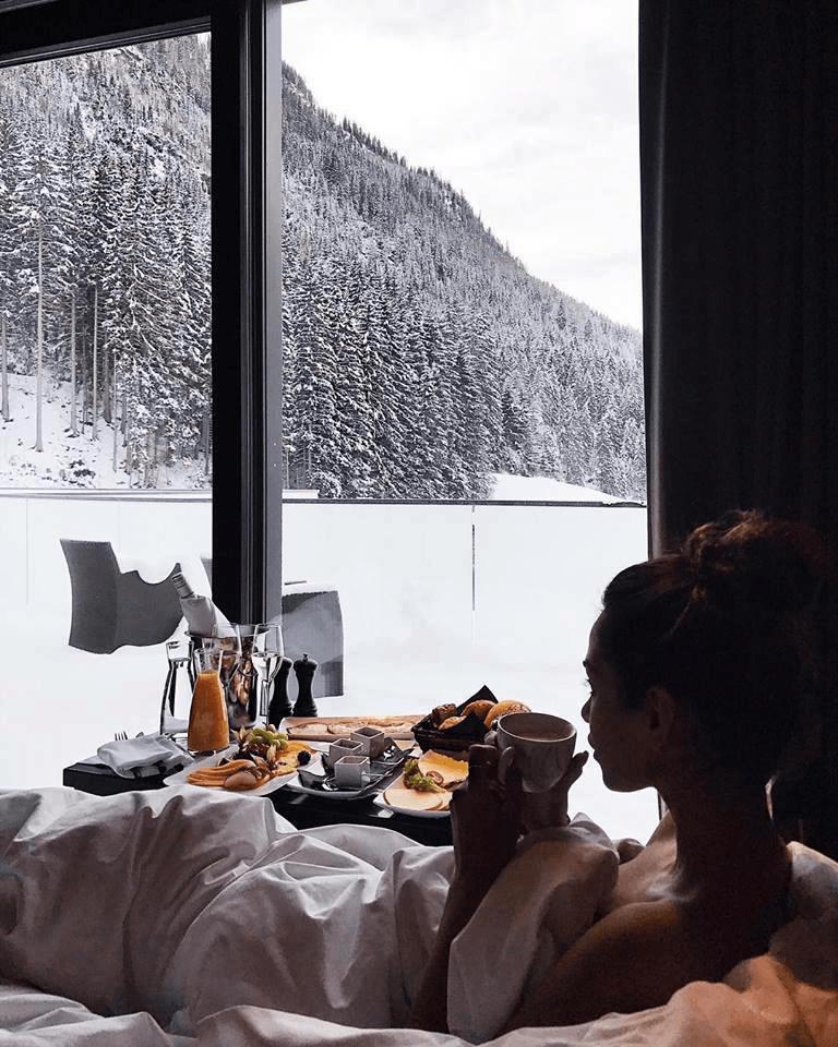 Fotos na neve comendo na cama perto da janela